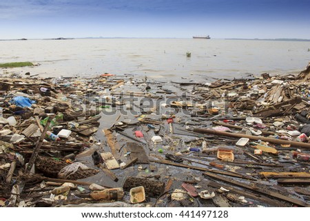 SANDAKAN, MALAYSIA - 23 JUNE 2016: Pollution environmental problem. Plastic bags and bottles on beach beside ocean due to no recycling or refuse disposal. - stock photo