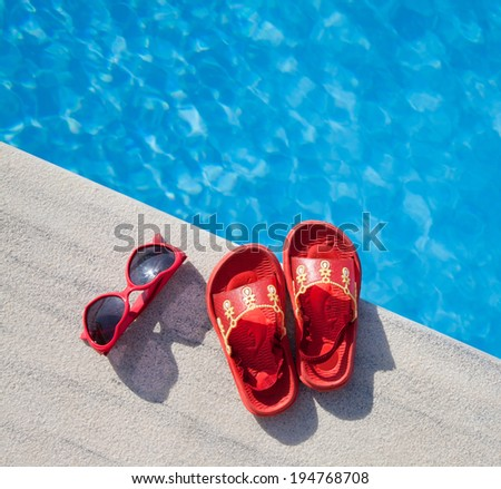sandal and sunglasses by the swimming pool  - stock photo