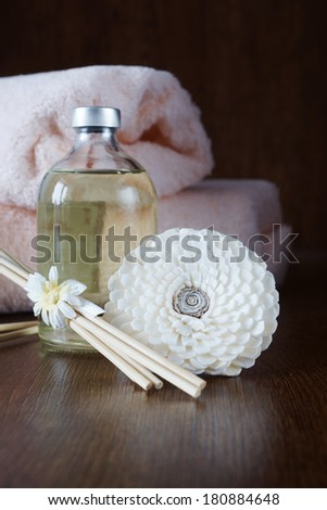 Sandal oil and sticks for aromatherapy on wooden surface - stock photo