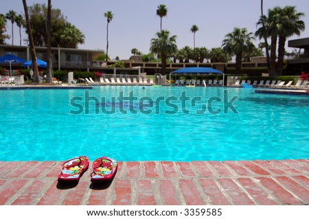 Sandals Next To Large Empty Swimming Pool In Palm Springs, California