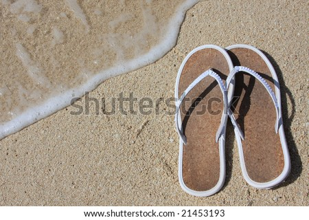 Sandals on beach sand with high tide - stock photo