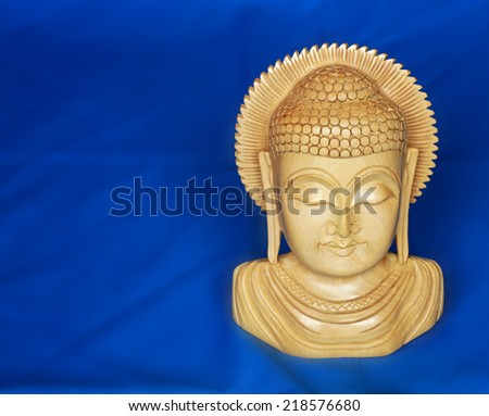 Sandalwood Buddha on blue background - stock photo