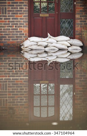 Sandbags Outside Front Door Of Flooded House - stock photo