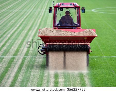 Sandblasting of football field - stock photo