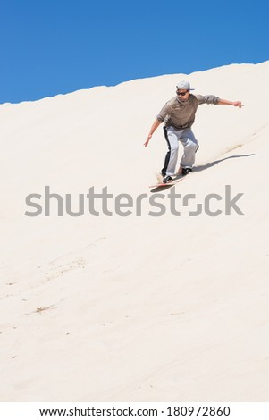 Sandboarding at sand dunes in Little Sahara, Kangaroo Island, South Australia  - stock photo