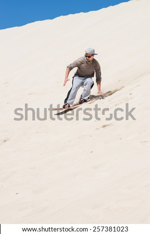 Sandboarding at sand dunes in Little Sahara, Kangaroo Island, South Australia.Focus on the man
