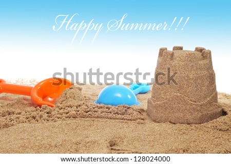 sandcastle and shovels on the sand of a beach and the sentence happy summer - stock photo