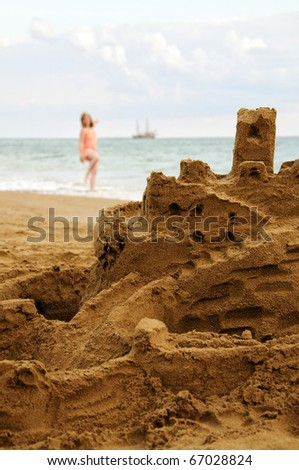 Sandcastle by the sea, with young woman and ship on background - stock photo