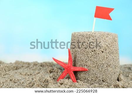 Sandcastle with starfish on sandy beach  - stock photo