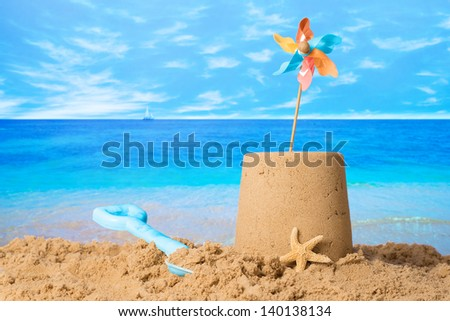 Sandcastle with windmill on summer beach - stock photo