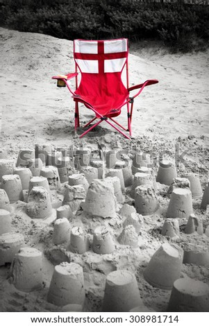 Sandcastles on a beach with a chair in the colors of England