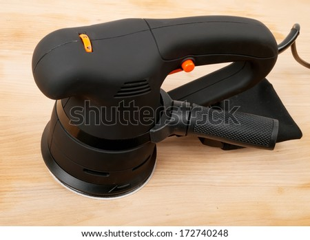 sander machine on a wooden surface - stock photo