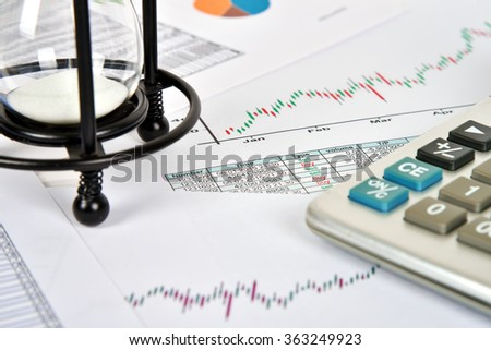 sandglass, financial and business charts and report on table