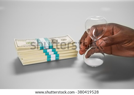Sandglass near money pack. Start the countdown. Prescious things. Mind your choice. - stock photo