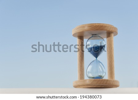 Sandglass with blue background. Natural light.