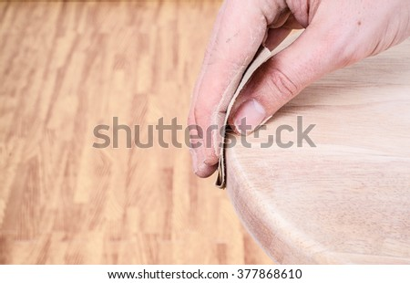 Sanding and smoothing a wooden seat top with sandpaper. - stock photo