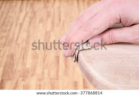 Sanding and smoothing a wooden seat top with sandpaper. Landscape with copy space. - stock photo