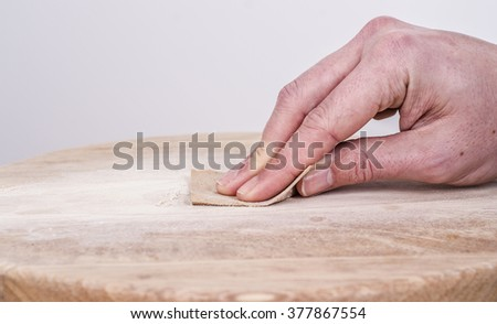 Sanding and smoothing a wooden seat with sandpaper. - stock photo