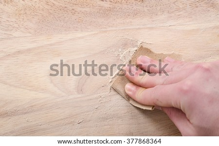 Sanding and smoothing wood with sandpaper. - stock photo