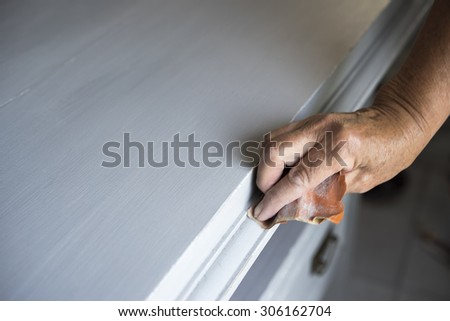 Sandpapering an vintage chest of drawers - stock photo
