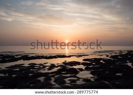 Sandstone rocks at the sea on beautiful sunrise - stock photo