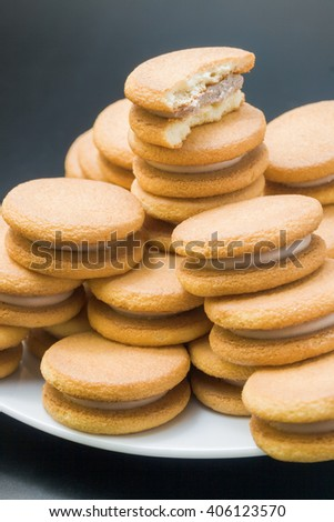 Sandwich biscuits. Sweet sandwich-biscuits filled with hazelnut cream arranged in a pyramid in a white plate with one bitten biscuit on top close up on dark neutral background. - stock photo