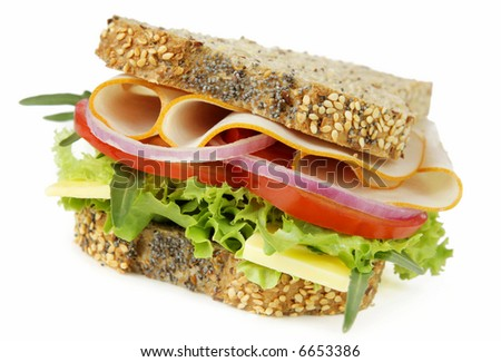 Sandwich filled with chicken or turkey slices, with fresh salad and cheese, on seeded bread