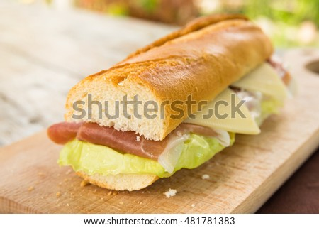 Sandwich filled with prosciutto crudo ham, cheese and lettuce