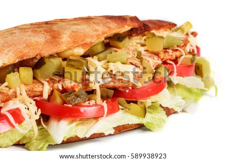 Sandwich from fresh pita bread with fillet grilled chicken, lettuce, slices of fresh tomatoes, pickles and cheese on white background