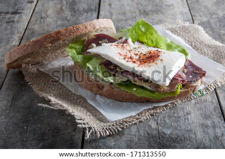 Sandwich from smoked meat on old wooden table - stock photo