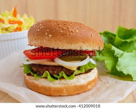 Sandwich home of the hamburger buns soft, juicy burger, cheese, tomato, parsley. Salad savoy cabbage. Fast food. - stock photo