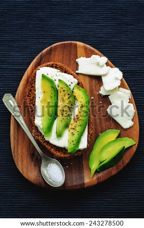sandwich of rye bread with avocado and goat cheese. tinting. selective focus - stock photo