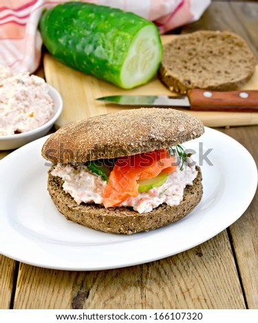 Sandwich of rye bread with cream, cucumber, dill and salmon on a plate on a wooden board - stock photo