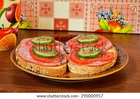 Sandwich on a plate. Photo of a two sandwiches made with ham, tomato, cucumber and garnished with pepper.