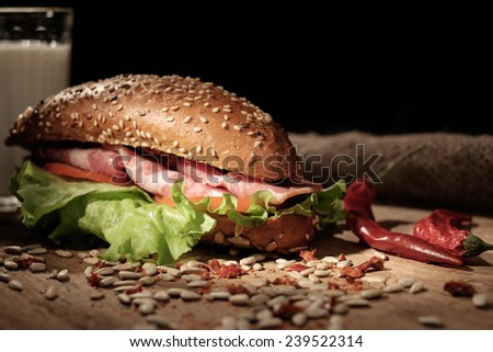 Sandwich on a wooden table with slices of bacon, lettuce and tomatoes. - stock photo