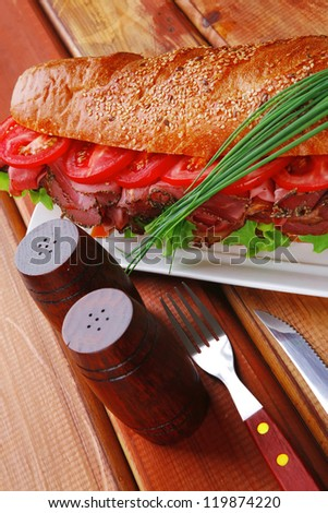 sandwich on plate : french baguette with smoked sausage on white plate over wooden table