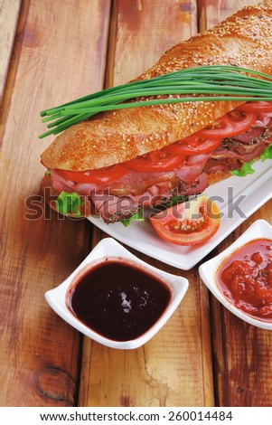 sandwich on plate : french long baguette with smoked chicken sausage on plate with sauces over wood - stock photo