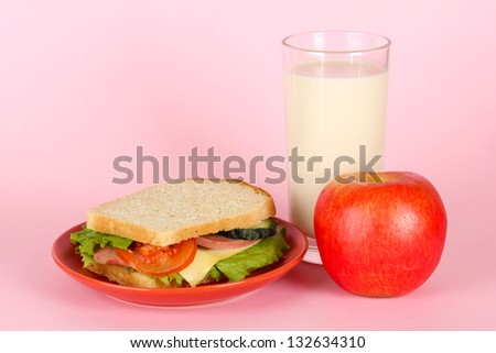 Sandwich on plate with apple and milk on pink background - stock photo