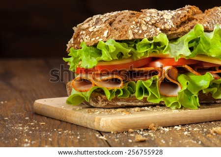 Sandwich on the wooden table - stock photo