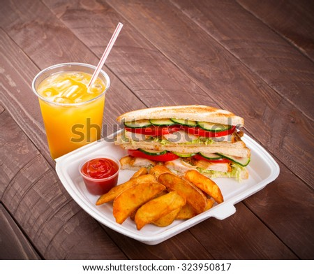 Sandwich, potatoes and juice on wood background