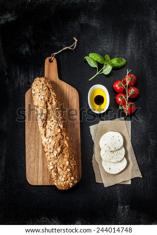Sandwich recipe - bread roll, mozzarella cheese, cherry tomatoes and basil. Ingredients on black chalkboard from above. Poster layout with free text space. - stock photo