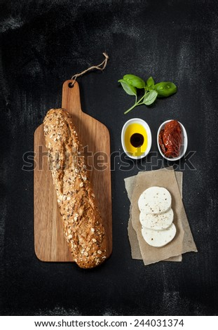 Sandwich recipe - bread roll, mozzarella cheese, sun dried tomatoes and basil. Ingredients on black chalkboard from above. Poster layout with free text space. - stock photo