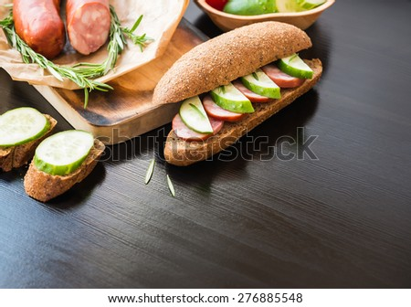Sandwich. Rye Baguette with Sausage and cucumbers. - stock photo