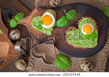 Sandwich with avocado paste and egg in the shape of heart - stock photo