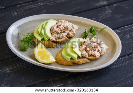 sandwich with avocado, salmon and whole wheat bread on an oval plate on a dark wooden surface, a healthy snack or Breakfast - stock photo