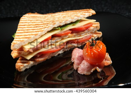 sandwich with Bacon and vegetables on black background - stock photo