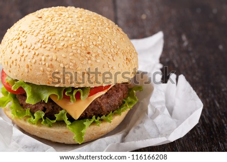 Sandwich with bacon and vegetables on wooden table - stock photo