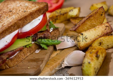 Sandwich with bacon, avocado and sauce. Toast with potatoes.