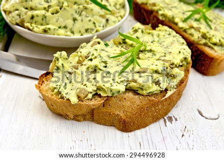 Sandwich with butter from spinach and pickles, a knife on the background light wooden boards