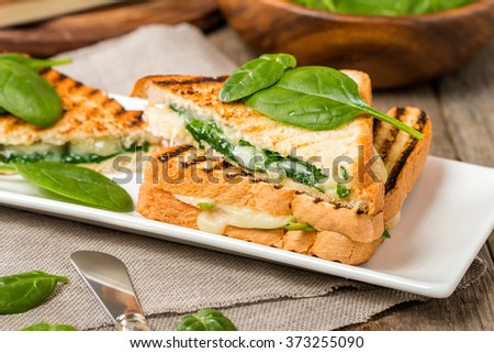 sandwich with cheese and spinach on wooden background - stock photo